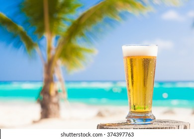 glass of cool beer on table near beach