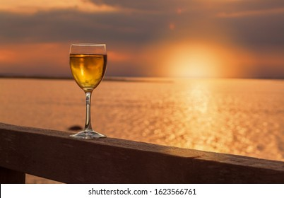 A glass with a cool drink standing on a wooden balustrade in the foreground of the seaside where you can see the sun down with golden light.