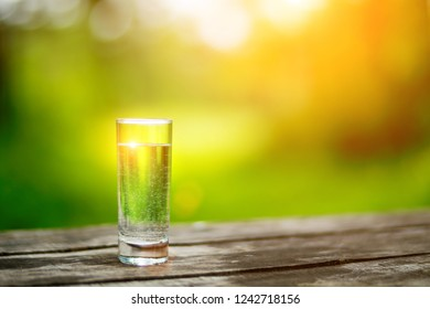 The glass of cool fresh water on a wooden table outdoors