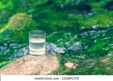 The glass of cool fresh water on nature background
