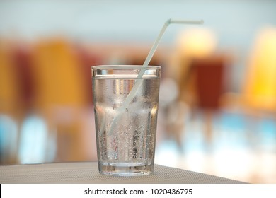 A glass of cool mineral sparkling water is on the table in the summer cafe