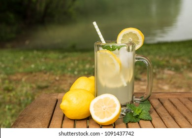 A glass of cool, refreshing lemonade next to the lake in summertime