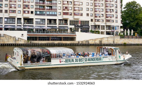 Glass covered, open air river tour boat glides through the waters of the Spree River pas restaurants and apartments in downtown Berlin, Germany.  August 2019.