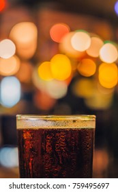 Glass of Craft Dark Beer Freshly Cold with Water Drops on the Beer Mug at a Pub or Alcohol Lounge Night Club Bar as Celebration or Joyful Party Time Out of Office Colorful Bokeh Light Blur Background