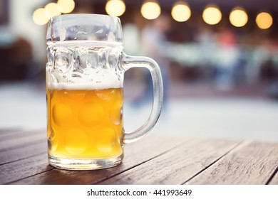 Glass of craft lager beer on pub table. Tapped unfiltered beer. Shallow depth of field
