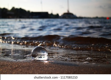 glass crystal ball in sand on the beach, against beautiful sea or ocean with sunny reflections, symbolizing the fragility of nature and the world