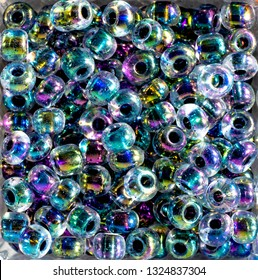 Glass crystal beads in compartment box for crafting own jewelry, close up, top down view. Multi-colored beads iridescent, holographic colors.