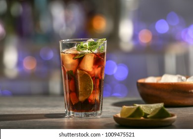 Glass with Cuba Libre cocktail on table against blurred background