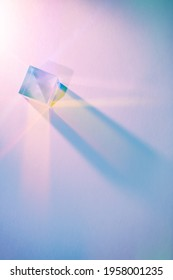 Glass cube with color spectrum rays. Abstract background with reflection and refraction of light. Shadow and rays of natural light effects.