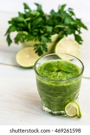 Glass of cucumber juice on white wooden background