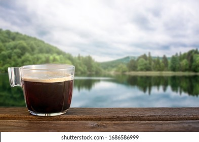 Glass cup of black coffee with lake in the forest blur background
