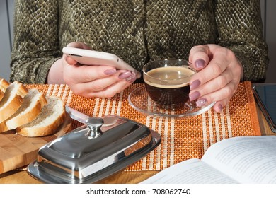 Glass cup with black coffee and phone in female hands with manicure
