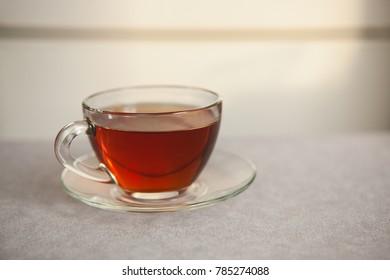 Glass cup of black tea on gray table