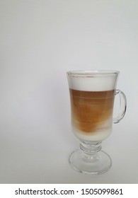 glass cup with cappuccino coffee and gray background