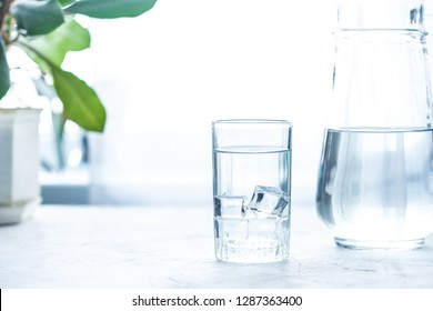 glass cup and carafe with water and ice on a white table