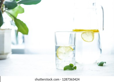 glass cup and a carafe of water, ice, mint and lemon on a white table