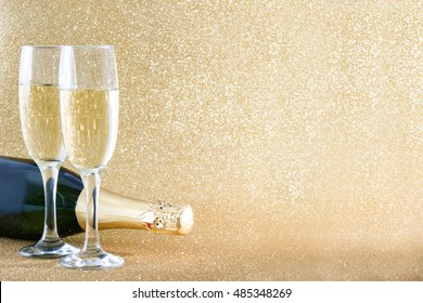 Glass cup with champagne bottle on golden brilliant background