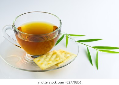glass cup of chinese tea and crackers on white background