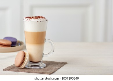 Glass cup of coffee latte and colorful macaroons on wooden table