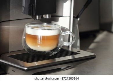 Glass cup of creamy cappuccino for perfect breakfast  maked at home  with modern fully automatic coffee machine.