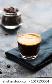 Glass cup of fresh coffee with thick golden foam froth on dark rustic background, espresso americano on black tissue with spoon of brown sugar and coffee beans, vertical copy space