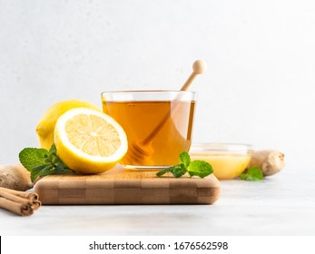 A glass cup of fresh green herbal tea with lemon, honey and green mint leaves. White background, close up view, copy space.