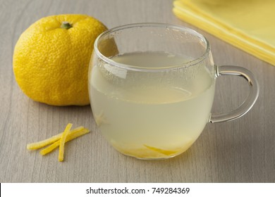 Glass cup with fresh Japanese Yuzu tea and a whole yuzu in the background