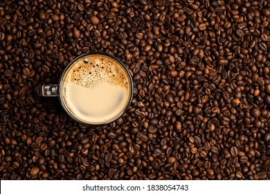 glass cup full of coffee over a background of coffee beans