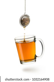 glass cup full of tea with tea infuser dropping, on white background