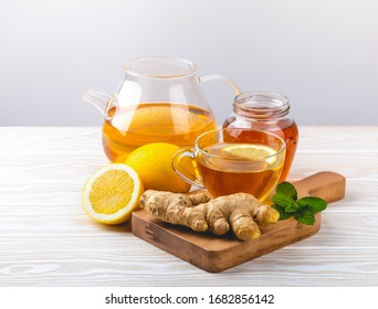 Glass cup with ginger and lemon tea, teapot, fresh mint, white wooden background. Homemade natural remedy against flu, cold, cough. Immunity stimulating hot beverage, natural medicine for good health