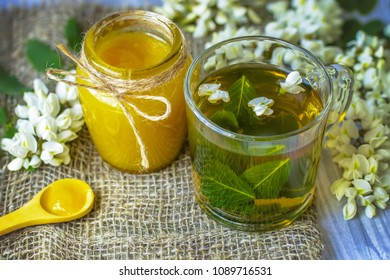 glass cup of herbal tea and acacia honey in jar closeup. herbal tea with honey from acacia as a concept of healthy nutrition. background with a cup of tea, honey and acacia flowers.