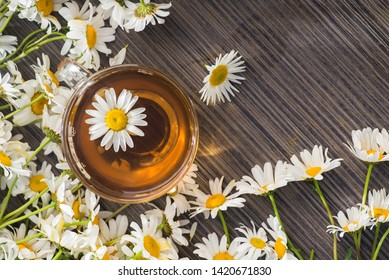 Glass cup with herbal tea with chamomile flowers on a wooden background. Healthy drink. top view. flat lay