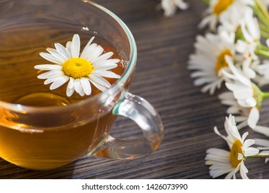 Glass cup with herbal tea with chamomile flowers on a wooden background. Healthy drink.