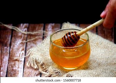 A glass cup of honey isolated on black background on the wooden table. Side view close up details.
