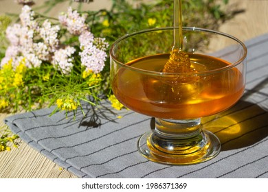 A glass cup with honey on a background of wildflowers. Honey with herbs. Health and benefits