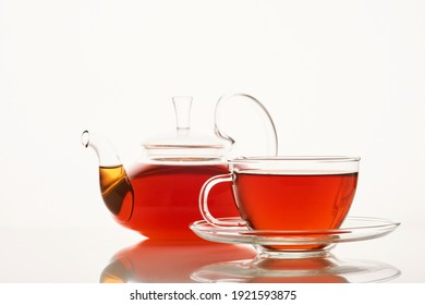 Glass cup of hot aromatic tea and teapot on white background