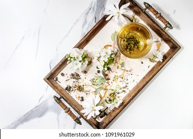 Glass cup of hot green tea on vintage tray with spring flowers white magnolia and cherry blooming branches over white marble texture background. Top view, space.