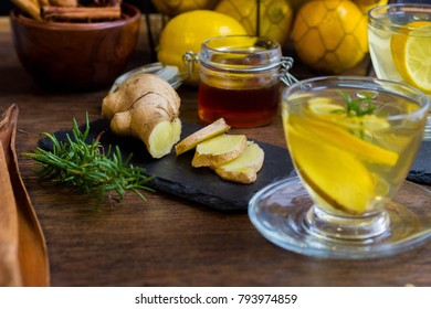 Glass cup of hot tea with mint, honey, ginger and lemon on dark background.