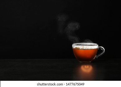 Glass cup of hot tea on table against black background, space for text