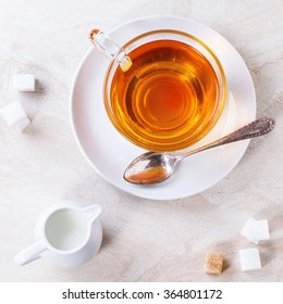 Glass cup of hot tea on saucer with sugar cubes, jug of milk over white marble backgtound. Top view. Square image