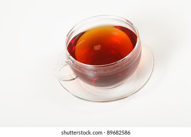 A glass cup of hot tea on a saucer. Focus on the bubbles.