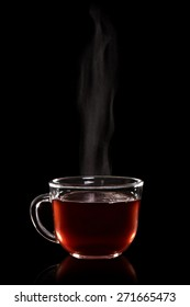 Glass cup of hot tea with vapor on a black background