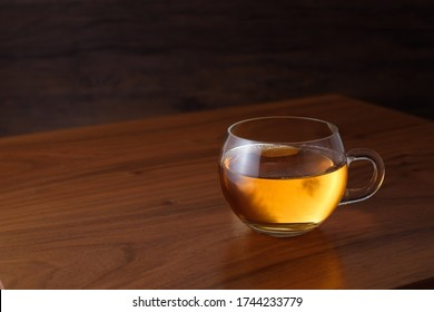 Glass cup of orange black tea on wooden table