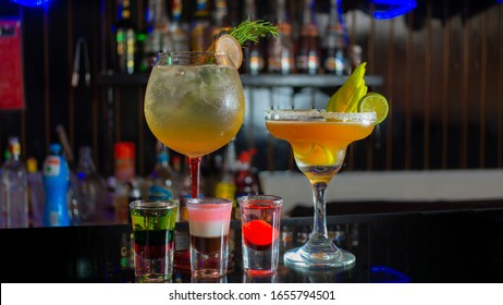 Glass cup with passion fruit margarita accompanied by three small glass glasses with tequila reflecting on the table of a bar with unfocused background