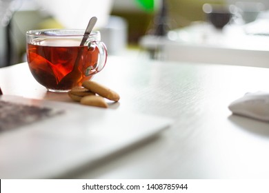 A glass cup with red or black tea bags on a white office desk with a laptop and mouse. Background bokeh. Tea break or loved job. Working in internet online or offline or in the office. Freelancers day