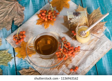 Glass cup with rowan berries, honey and honeycomb on a sackcloth. Closeup