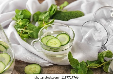 Glass cup of tasty cucumber water on white cloth