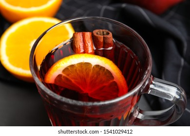 Glass cup of tasty mulled wine on black table, closeup