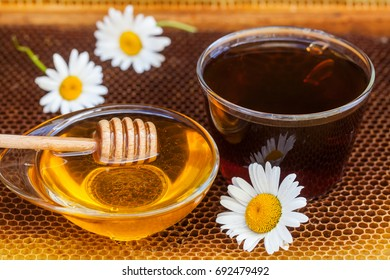 Glass cup tea with honey, wood stick and chamomile