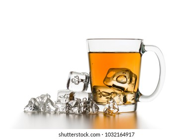 glass cup of tea with ice cubes on white table.